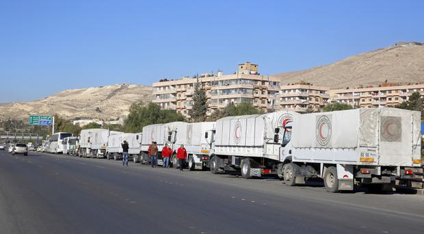 A convoy of humanitarian aid waits before making its way into government-besieged rebel-held towns in Syria (AP)