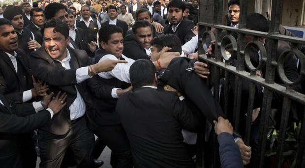 A lawyer (centre) who spoke to the media supporting student leader Kanhaiya Kumar is beaten up by other lawyers outside a Delhi court (AP)