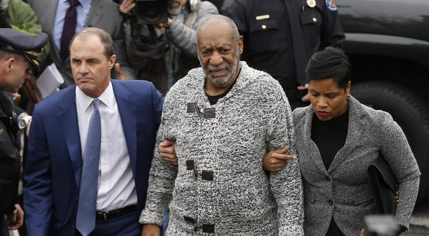 Bill Cosby, centre, arrives with his lawyers for a court hearing in December (AP)