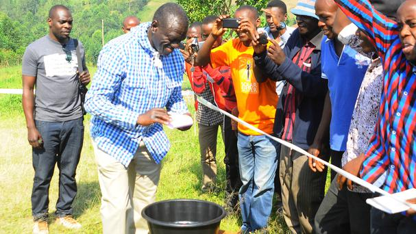 Kizza Besigye cleans his hands after casting his vote at his polling station near his country home in Rukungiri (AP)