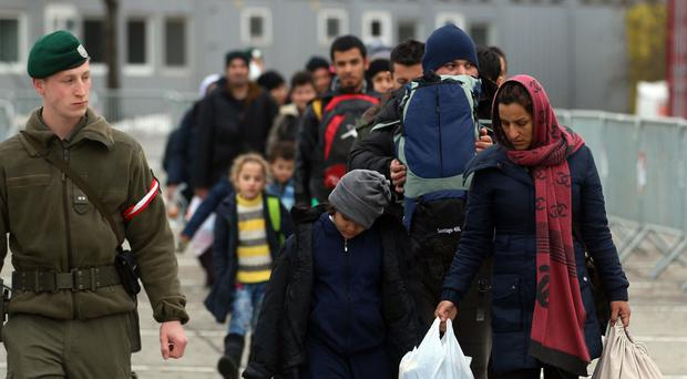 Migrants walk between registration tents at the border with Slovenia in Spielfeld, Austria (AP)