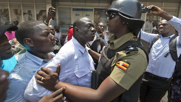 Opposition leader Kizza Besigye is confronted by riot police in Kampala (AP)