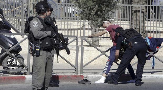 Police search a Palestinian near the scene of the attack in Jerusalem (AP)