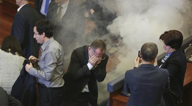 MPs clear the hall after a tear gas canister was released during a parliamentary session (AP)