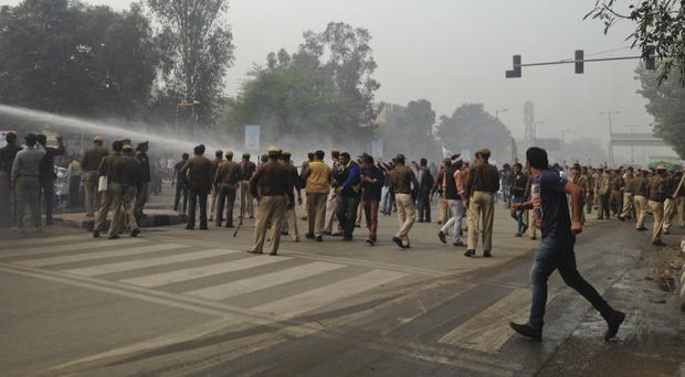 Police use water cannons to disperse protesters from the Jat agricultural community in New Delhi (AP)