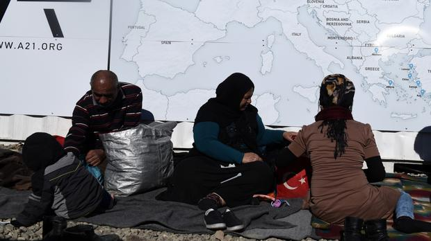 Refugees sit under a map of Europe at a refugee camp at the Greek-Macedonian border (AP)
