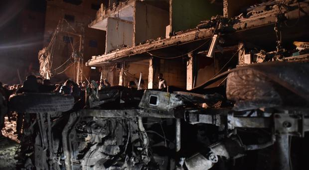 People gather in the aftermath of a multiple explosive attack in the Sayyida Zeinab area, south of Damascus, Syria (AP)