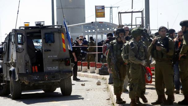 Israeli soldiers stand guard at the scene of an attack at the Gush Etzion junction in the West Bank (AP)