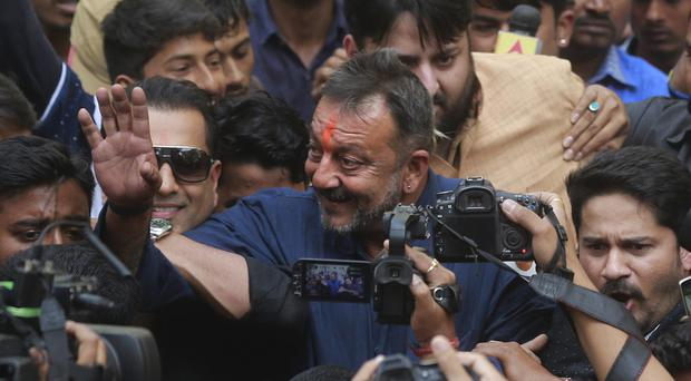 Bollywood actor Sanjay Dutt waves to his fans as he arrives at his residence in Mumbai, India (AP)