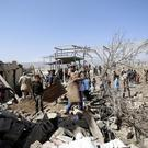 People gather at the site of a house destroyed by a Saudi-led airstrike in Sanaa, Yemen (AP)