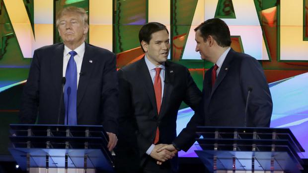 Donald Trump pauses as Republican rivals Marco Rubio, centre, and Ted Cruz share a handshake during the debate at The University of Houston (AP)