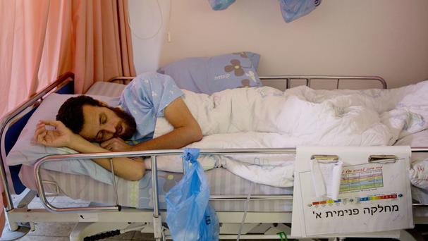 Palestinian journalist prisoner Mohammed al-Qeq lying in a hospital bed at the Emek Medical Centre in Afula (AP)