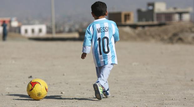 Murtaza Ahmadi, a five-year-old Afghan Lionel Messi fan, wearing a shirt signed by the footballer, in Kabul (AP)