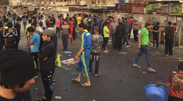 People gather at the scene of deadly bombing attacks in Sadr City, Baghdad, Iraq (AP)