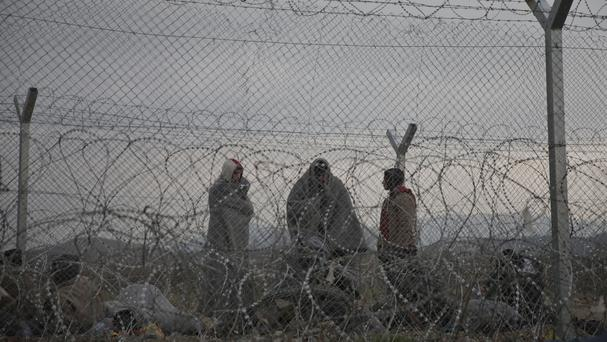 Refugees stand behind a fence reinforced with razor wire on the border line with Greece near the southern Macedonian town of Gevgelija (AP)