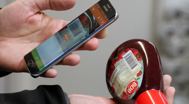 Swedish IT entrepreneur Robert Ilijason shows how to use a mobile phone to scan a purchase at his unmanned shop in the southern Sweden village of Viken (AP)