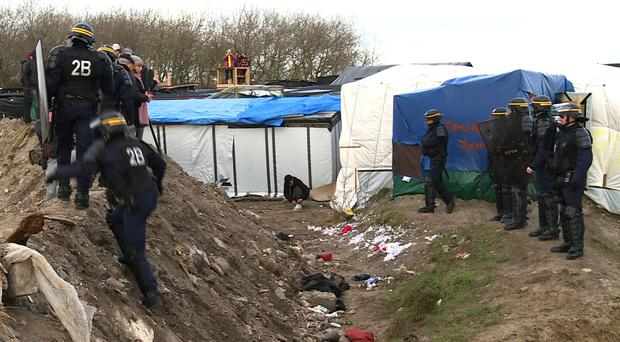 Police officers take positions to safeguard workers pulling down makeshift structures in Calais (AP)