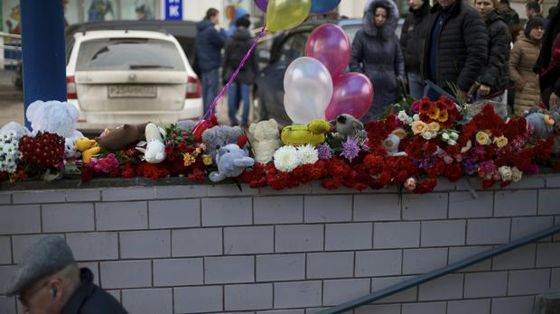 Flowers, children's toys and balloons have been left outside a subway station in Moscow (AP)