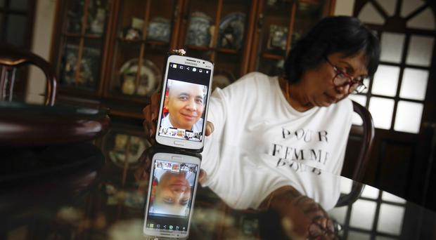 Sakinab Shah, the sister of Captain Zaharie Ahmad Shah, holds up her mobile phone with a picture of her brother (AP)