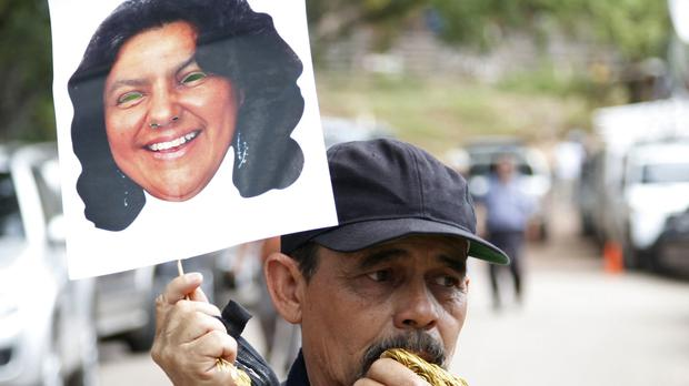 A man holds up a portrait of murdered Honduran indigenous leader and environmentalist Berta Caceres outside the coroner's office in Tegucigalpa (AP)