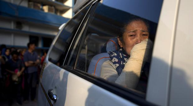 Nyima Yangzom, mother of Dorje Tsering, cries as she leaves with the body of her son from the hospital in New Delhi (AP)