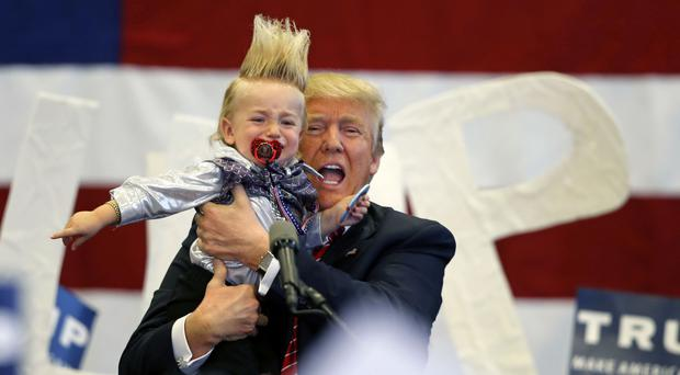 Republican presidential candidate Donald Trump holds up a child he pulled from the crowd in New Orleans (AP)