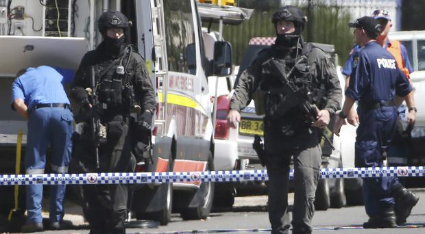 Armed police cordon off a street of an industrial section of Ingleburn, Sydney (AP)