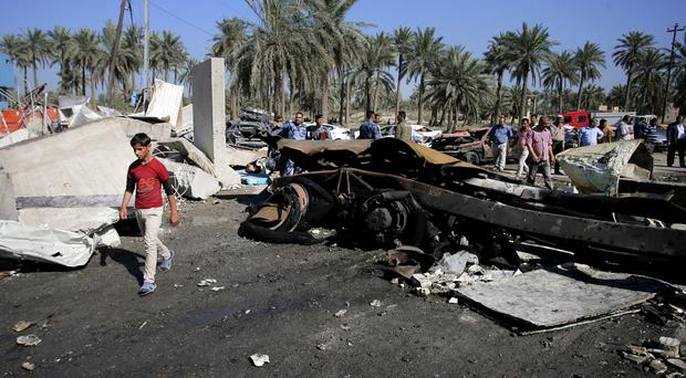 Civilians and security forces at the scene of a suicide bomb attack in Hillah, south of Baghdad (AP)