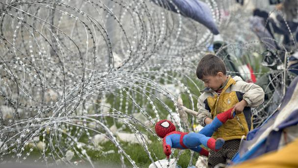 A boy untangles a Spiderman doll caught in barbed wire around the fence between Greece and Macedonia at the northern Greek border station of Idomeni (AP)