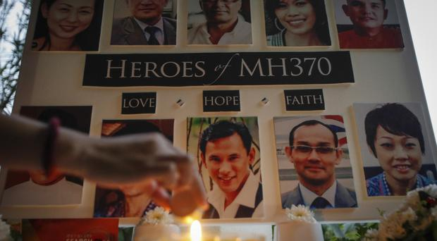 A Malaysian woman lights a candle for the ill-fated Malaysia Airlines Flight 370 at a church in Kuala Lumpur on the second anniversary of the plane's disappearance (AP)