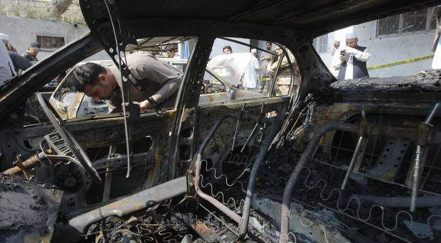 A Pakistani security official collects evidence at the site of a suicide bombing in Charsadda (AP)