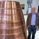 Jeff Bezos with a copper exhaust nozzle to be used on a Blue Origin space ship engine (AP)