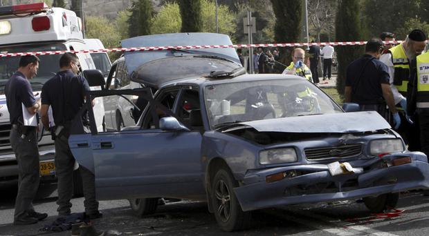 Police examine a car used in a shooting in Jerusalem (AP)