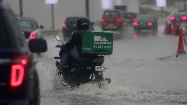 A delivery man rides his bike during heavy rain in Dubai (AP)