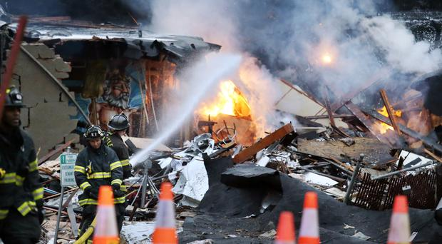Firefighters pour water on flames in the rubble left from an early morning explosion in Seattle (AP)