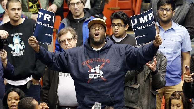 A protester holds up a ripped campaign sign for Republican presidential candidate Donald Trump on the campus of the University of Illinois Chicago (AP)