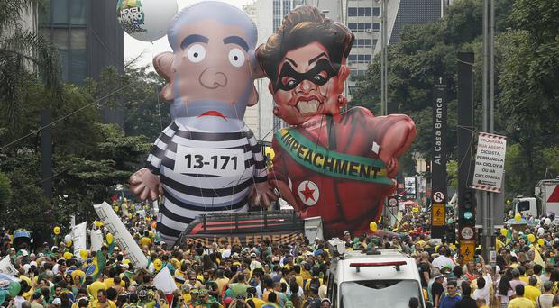 Demonstrators in Sao Paulo parade inflatable dolls of Brazil's former president Luiz Inacio Lula da Silva in prison garb and Dilma Rousseff dressed as a thief (AP)