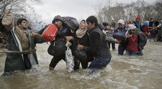 A woman is supported by two men while crossing a river as migrants attempt to reach Macedonia (AP)