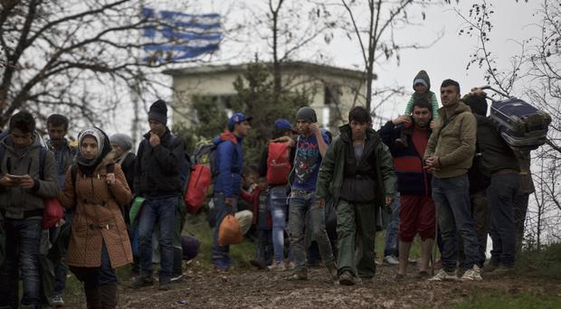 A group of migrants walk past a Greek border post north of Idomeni, attempting to reach Macedonia (AP)