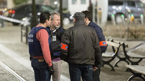 Police officers speak to each other during an apartment raid in Brussels (AP)