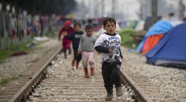 Children run on railway tracks at the northern Greek border point of Idomeni (AP)