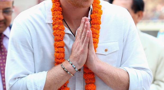 Prince Harry is greeted with a garland and a tilak (a mark placed on the forehead as a sign of respect) at Bhaktapur in Kathmandu, on the second day of his tour