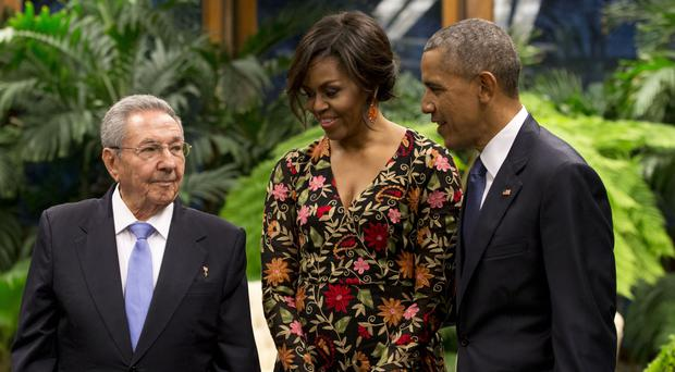 President Obama and his wife Michelle talk with Cuban president Raul Castro as they arrive for a state dinner at the Palace of the Revolution in Havana (AP)
