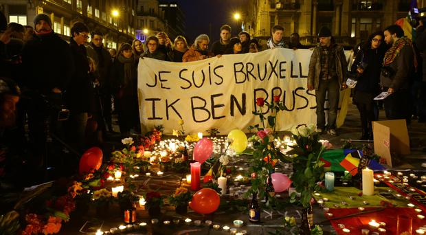 People gather at the Place de la Bourse in Brussels to leave messages and tributes