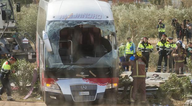 Emergency services personnel stand at the scene of the bus crash on the AP7 highway near Freginals in Spain (AP)