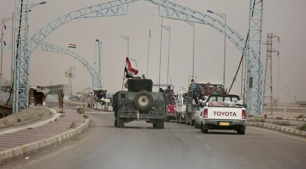 A convoy of families fleeing Islamic State-held Hit in Iraq wait at a checkpoint on the western edge of Ramadi, as Iraqi forces launch an operation to recapture IS-held Mosul (AP)