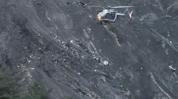 A rescue helicopter flies over debris of the Germanwings passenger jet (AP)