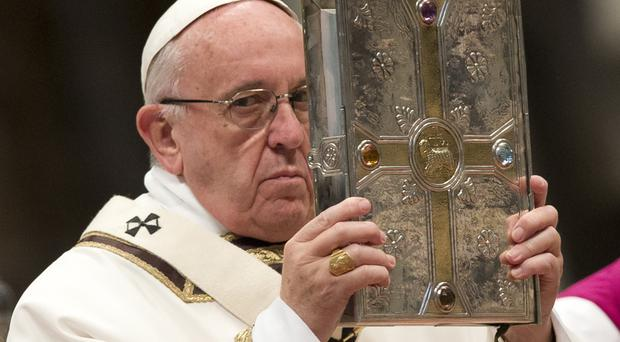 Pope Francis holds the Gospel book as he leads a Chrism Mass in St Peter's Basilica at the Vatican (AP)