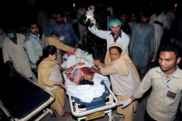 Pakistani relatives and emergency workers after a suicide bomb went off in Lahore