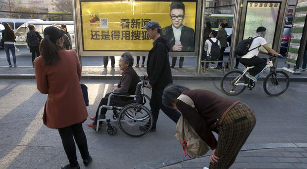 Pedestrians pass by an advertisement for a Chinese news web portal in Beijing (AP)